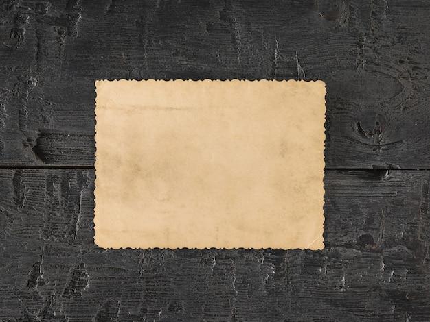 Een vel oud papier op een zwarte houten tafel. retro schrijfpapier. plat leggen het uitzicht vanaf de top.