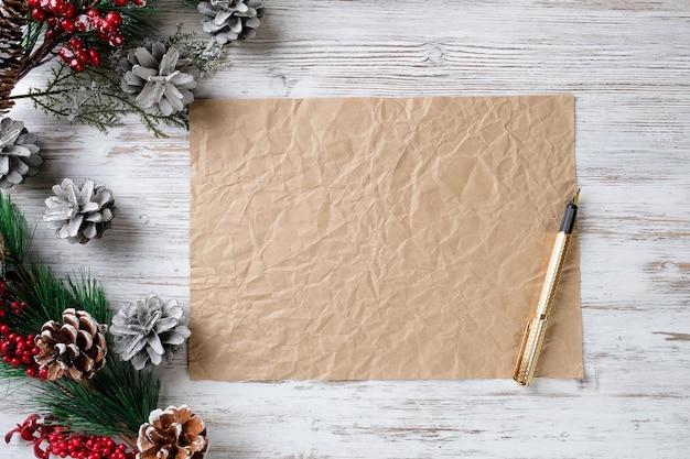 Een vel papier, een pen en dennentakken op een houten tafel. kerstmis en nieuwjaar concept