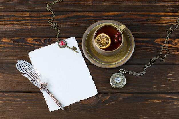 Een vel papier, een vulpen, een oud zakhorloge, een sleutel en een kopje thee