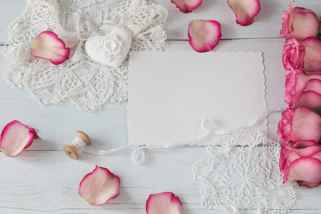 Een vel papier, roze rozen, rozenblaadjes en veters
