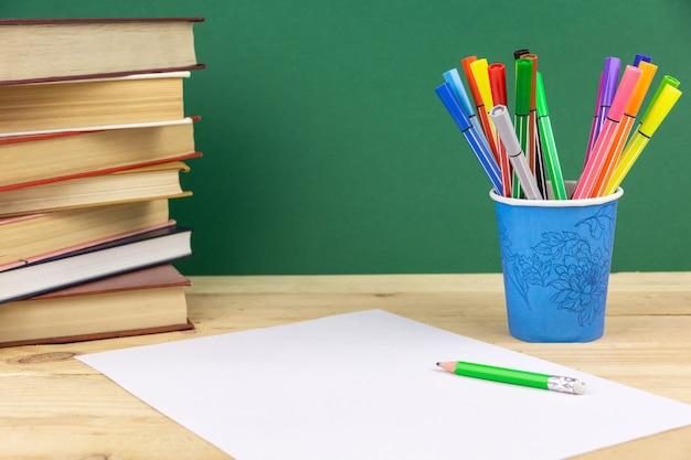 Een vel wit papier en een potlood bij een stapel boeken en stiften
