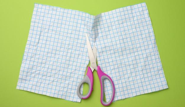 Een vel wit papier in tweeën gesneden met een schaar in een blauwe doos op een groen oppervlak, bovenaanzicht