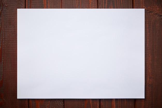 Een vel wit papier op een donkere houten achtergrond.