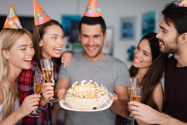 Een vent is jarig en zijn vrienden feliciteren hem.