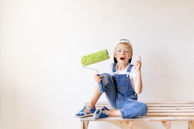 Een verbaasd kind bouwer zit op een ladder van de bouw in een appartement met witte muren en een roller in zijn handen en toont een duim omhoog, plaats voor tekst, reparatieconcept