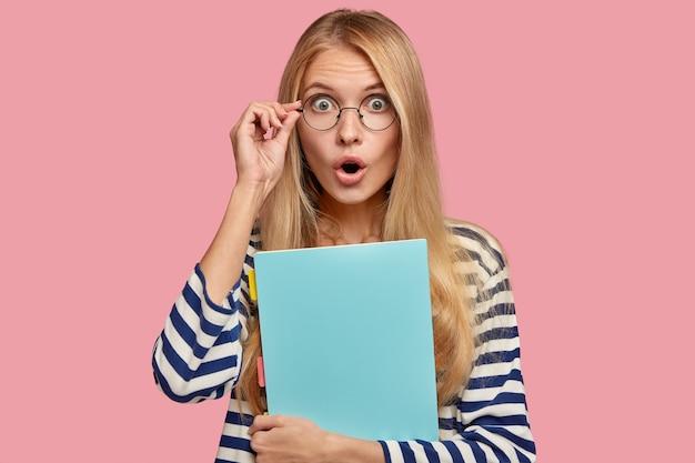 Een verbaasd, lichtharig schoolmeisje met een verbijsterde uitdrukking houdt de hand op de brilrand, ziet iets ongelooflijks