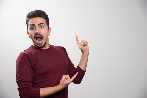 Een verbaasde brunette man met een vinger omhoog.