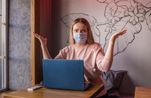 Een verbaasde gemaskerde vrouw zit in een café met een laptop