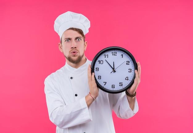 Een verbaasde jonge, bebaarde chef-kok in wit uniform toont de tijd terwijl hij een wandklok op een roze muur houdt