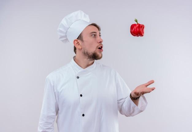 Een verbaasde jonge, bebaarde chef-kokmens die een wit fornuisuniform draagt en een hoed die rode paprika in de lucht op een witte muur gooit
