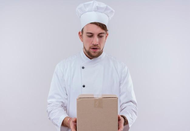 Een verbaasde jonge, bebaarde chef-kokmens in wit uniform die een leveringsdoos houdt en ernaar kijkt op een witte muur