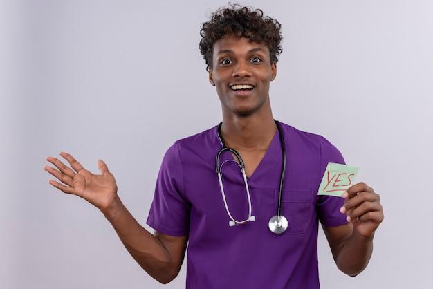 Een verbaasde jonge knappe donkere mannelijke arts met krullend haar in violet uniform met een stethoscoop die een papieren kaart toont met het woord ja