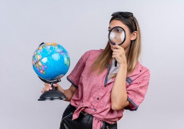 Een verbaasde jonge vrouw met een rood shirt in een zonnebril die een wereldbol vasthoudt terwijl ze ernaar kijkt met een vergrootglas