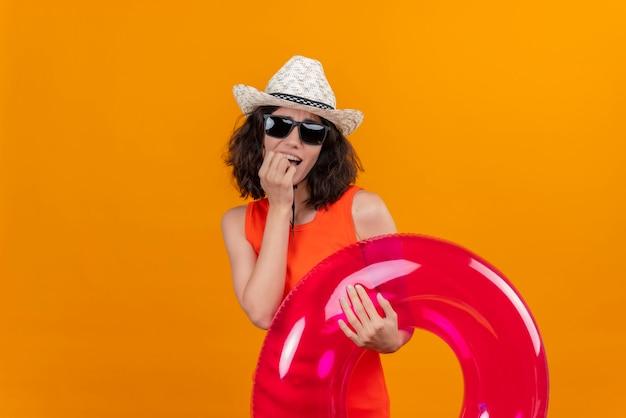 Een verbaasde jonge vrouw met kort haar in een oranje overhemd met zonnehoed en zonnebril die opblaasbare ring met hand op mond houdt