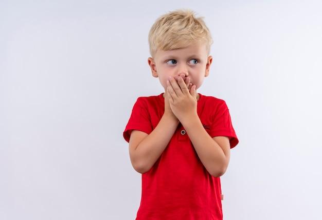 Een verbaasde kleine schattige blonde jongen in een rood t-shirt die handen op zijn mond houdt terwijl hij op een witte muur kijkt
