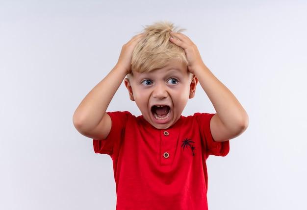 Een verbaasde kleine schattige blonde jongen in een rood t-shirt die het hoofd met de handen vasthoudt terwijl hij op een witte muur kijkt