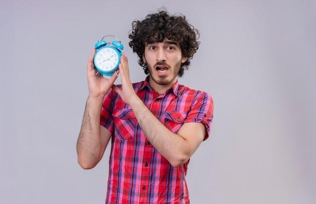 Een verbaasde knappe man met krullend haar in een geruit overhemd met een blauwe wekker