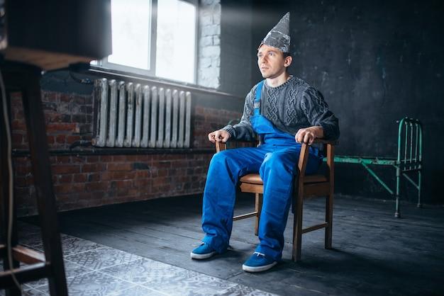 Een verbaasde man in aluminiumfoliehelm zit in stoel