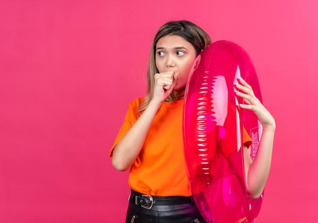 Een verbaasde mooie jonge vrouw in een oranje t-shirt die kant kijkt met de hand op de mond terwijl ze een roze opblaasbare ring aan een roze muur vasthoudt