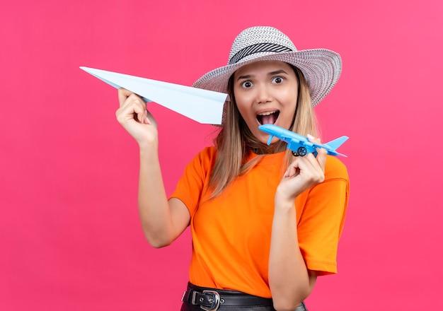 Een verbaasde mooie jonge vrouw in een oranje t-shirt met een zonnehoed die vliegt met een papieren vliegtuigje terwijl ze een blauw speelgoedvliegtuig op een roze muur houdt