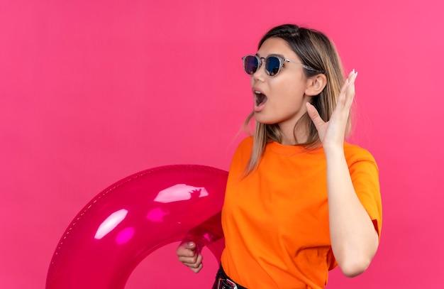 Een verbaasde mooie jonge vrouw in een oranje t-shirt met zonnebril die hand opstak met open mond terwijl ze een roze opblaasbare ring op een roze muur vasthoudt