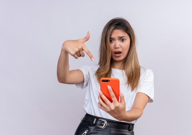 Een verbaasde mooie jonge vrouw in wit t-shirt wijzend met wijsvinger tijdens het kijken naar mobiele telefoon op een witte muur