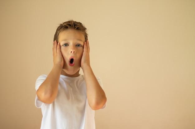 Een verbaasde of bange jongen van 7-10 jaar in een wit t-shirt staat en schreeuwt met zijn handen op zijn wangen.