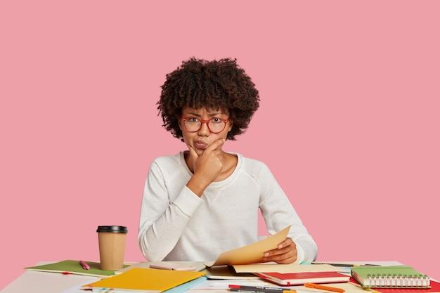 Een verbaasde vrouwelijke recensent of manager tuit zijn lippen terwijl hij rekeningen bestudeert, met veel objecten achter het bureau zit