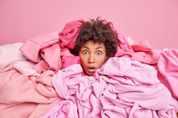 Een verbijsterde, emotionele vrouw die geobsedeerd is door het kopen van kleding bedekt met een grote hoop kleding, kan niet geloven dat haar ogen geïsoleerd over een roze muur de lenteschoonmaak in de kledingkast doen. rommelige doek