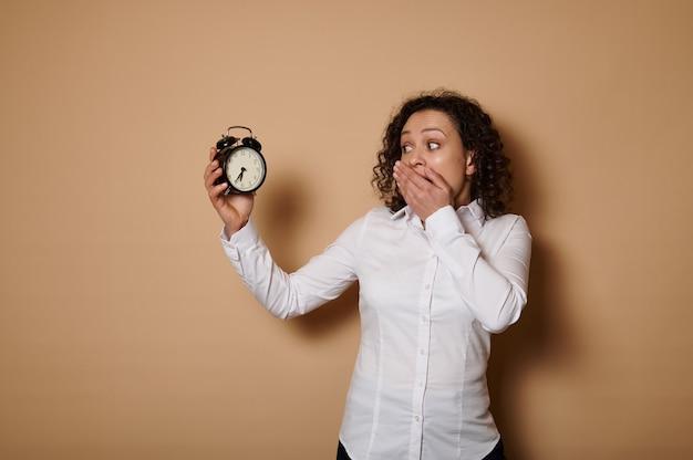 Een verbijsterde spaanse gekrulde vrouw houdt een wekker in haar handen en kijkt er met afgrijzen naar, terwijl ze haar mond bedekt met haar hand.