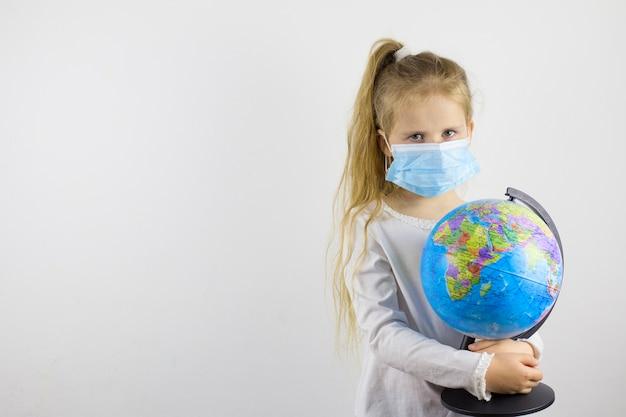 Een verdrietig kind in een beschermend masker en houdt een wereldbol vast. het concept om de wereld te isoleren van een nieuwe generatie virus