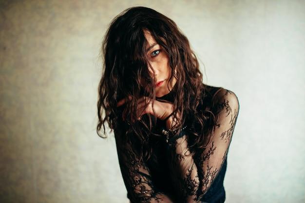 Een verdrietig meisje met zwart haar en blauwe ogen zit alleen in het midden van de kamer.