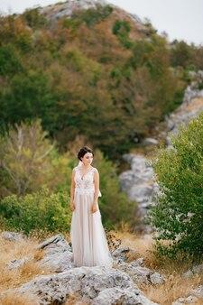 Een verfijnde bruid in een delicate kanten jurk staat op de rotsen