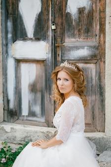Een verfijnde bruid met tiara zit in de buurt van een oude houten deur in de oude stad van perast close-up