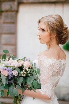 Een verfijnde bruid staat met een bruidsboeket in haar handen bij een witte houten deur in de