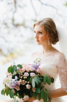 Een verfijnde bruid staat met een bruidsboeket in haar handen onder de takken van een boom