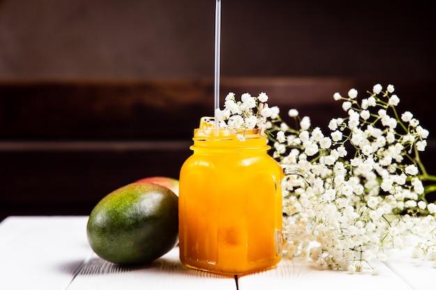 Een verfrissende mango limonade in een pot, op witte houten tafel