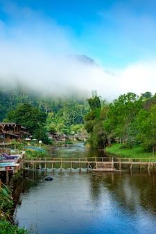 Een verfrissende ochtend aan de rivier in een klein dorp er is een huis aan het water achter een met mist bedekte berg bo kluea district, nan provincie, thailand