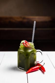 Een verfrissende zomer limonade met rode chili peper, in een pot, op witte houten tafel