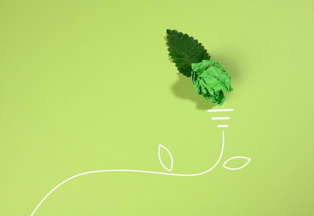 Een verfrommeld vel papier en een groen blad op een groen oppervlak, de vorm van een gloeilamp. energiebesparend concept, nieuw creatief idee, plat gelegd