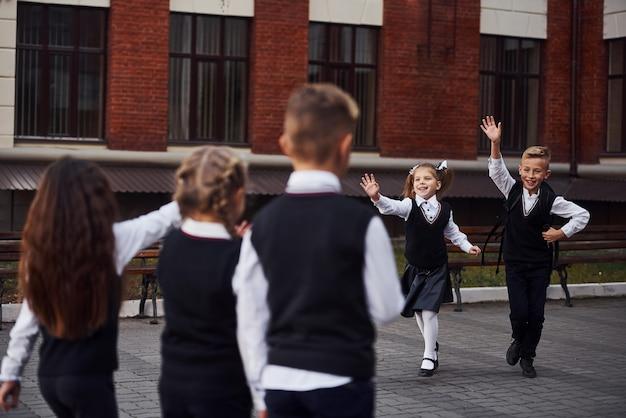 Een vergadering hebben. groep kinderen in schooluniform dat buiten samen is in de buurt van het onderwijsgebouw.