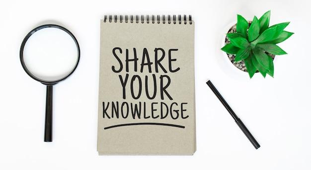 Een vergrootglas, een leeg bruin notitieboekje op een witte tafel. deel je kennis-teken