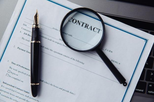 Een vergrootglas op het contract dat op een toetsenbord ligt.