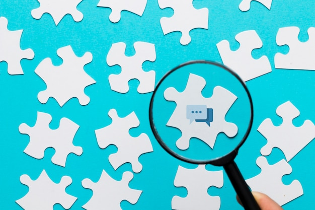 Een vergrootglas van de persoonsholding over het berichtpictogram op witte raadsel tegen blauwe achtergrond