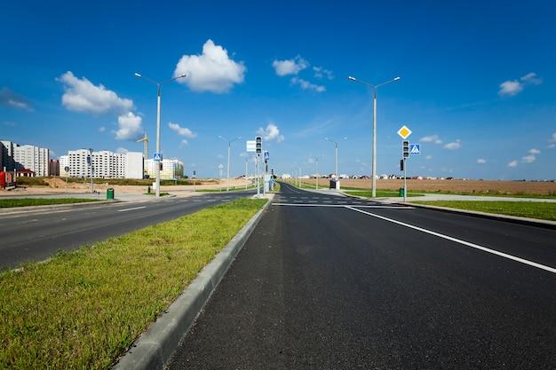 Een verharde weg die naar de bouwplaats leidt waar huizen met meerdere verdiepingen zijn gebouwd