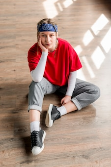 Een verhoogde mening van nadenkende jonge vrouwelijke danserszitting op harde vloer