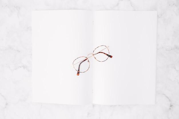 Een verhoogde mening van oogglazen over leeg witboek op marmeren achtergrond