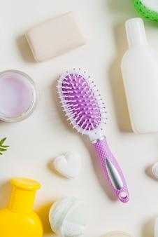 Een verhoogde weergave van haarborstel met cosmetische producten tegen een witte achtergrond