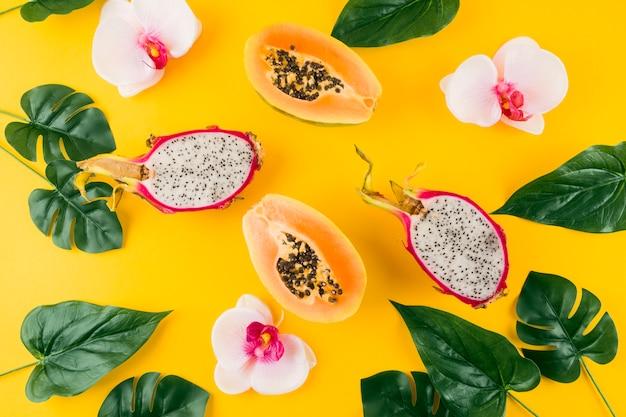Een verhoogde weergave van kunstmatige bladeren met orchideebloem; gehalveerde draak en papaja op gele achtergrond