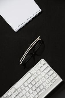 Een verhoogde weergave van spiraalvormige notitieblok; brillen en toetsenbord op zwart bureau